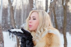 Pretty young woman in fur coat blowing on snow outdoor. At winter day in forest Stock Photography