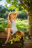 Pretty, young woman gardening in her garden. Harvesting organic apples - looking very happy with the results Royalty Free Stock Photography