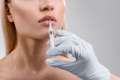 Pretty young woman getting collagen injection procedure stock photo