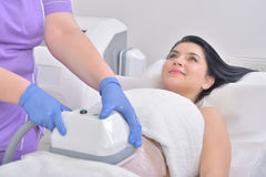 Pretty young woman getting cryolipolyse fat treatment in profess. Ional cosmetic cabinet Royalty Free Stock Images