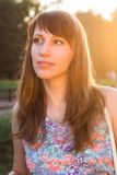 Pretty young woman glance away at summer day. Hipster caucasian girl dreaming at sunset beams Royalty Free Stock Image