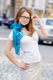 Pretty young woman with glasses against a street background Royalty Free Stock Image