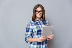 Pretty young woman in glasses holding tablet Stock Photography