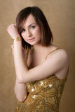 Pretty Young Woman in Gold Dress with Gold Watch Royalty Free Stock Images