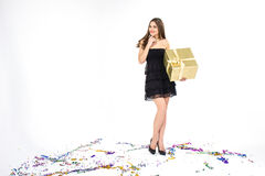 Pretty young woman with golden present box and confetti smiles Royalty Free Stock Photos