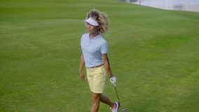 Pretty young woman golfer strolling on the course stock video