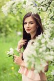Pretty young woman on green leaves and spring apple flowers. Background Stock Photography