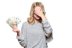 Pretty young woman in grey sweater holding bunch of Euro banknotes, covering her eyes with hand, isolated on white background. royalty free stock image