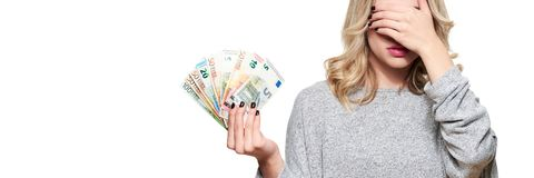 Pretty young woman in grey sweater holding bunch of Euro banknotes, covering her eyes with hand, isolated on white. royalty free stock photo