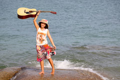 Pretty young woman with guitar on beach Stock Images