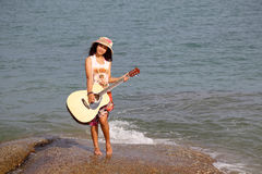 Pretty young woman with guitar on stone near beach Stock Photography