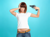 Pretty young woman with gun at head Royalty Free Stock Photography