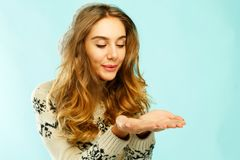 Pretty young woman with hands blowing on them over blue backgrou Stock Photos