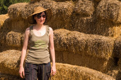 Pretty young woman with hat leaning to straw bales on a sunny day. Royalty Free Stock Image