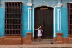 A pretty young woman with hat located at the door of an old colonial house in the colonial town of Trinidad Cuba royalty free stock photos