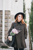 Pretty young woman in hat posing with coffee and flowers in bag Royalty Free Stock Images