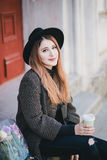 Pretty young woman in hat posing with coffee and flowers in bag Royalty Free Stock Photography