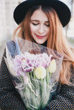 Pretty young woman in hat posing with flowers in bag Royalty Free Stock Image