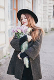 Pretty young woman in hat posing with flowers in bag Stock Photo