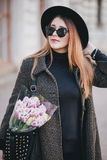 Pretty young woman in hat posing with flowers in bag Royalty Free Stock Photo