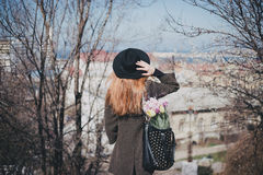 Pretty young woman in hat posing with flowers in bag Royalty Free Stock Photography