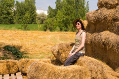 Pretty happy woman with hat sitting on straw bales and getting some rest. Stock Photo