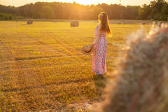 Pretty young woman in hat standing near hay bale Stock Images