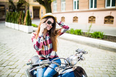Pretty young woman in hat using smartphone while sitting on motorbike. Young woman in hat using smartphone while sitting on motorbike Royalty Free Stock Photo