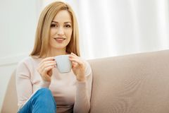 Pretty young woman having a coffee break. Coffee break. Beautiful alert dark-eyed slim blond woman holding a cup and wearing jeans and a beige sweater and Stock Image
