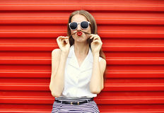 Pretty young woman having fun shows moustache hair over red Stock Image