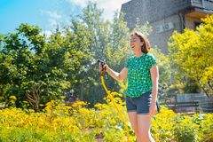 Pretty young woman having fun in summer garden with garden hose splashing rain. Concept of summer joy and hobby. Close up stock photo