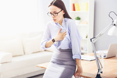 Pretty young woman having heartache and leaning on the table. Shocking news. Pretty bespectacled woman leaning on the table and putting hand on her heart while stock photo