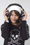 Pretty young woman with headphones. And a  cap Royalty Free Stock Image