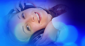 Pretty young woman in headphones listening music, blue lights background Stock Image