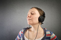 Pretty young woman with headphones listening to music. Royalty Free Stock Photo