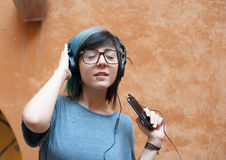 Pretty young woman with headphones and mobile phone Royalty Free Stock Image
