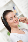 Pretty young woman with a headset Royalty Free Stock Photography