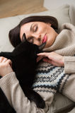 Pretty young woman with her black cat Stock Photography