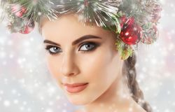 A pretty young woman, on her head a beautiful wreath of spruce with cones and balls. stock image