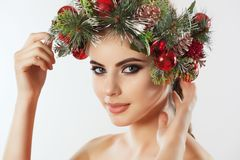 A pretty young woman, on her head a beautiful wreath of spruce with cones and balls. royalty free stock photo