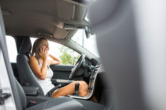 Pretty, young woman in her modern car calling on her call phone Royalty Free Stock Images