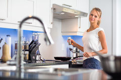 Pretty, young woman in her modern, clean and bright kitchen Royalty Free Stock Images