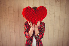 Pretty young woman hiding her face behind heart pillow Royalty Free Stock Photography