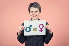 Pretty young woman hipster holding a white paper sheet with message for gender equality concept as male and female symbol are. Equal. Sex sign social issue, no stock photo
