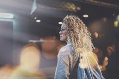 Pretty young woman hipster in stylish clothing wearing eye glasses traveling in the european night city. Bokeh and. Flares effect on blurred background royalty free stock photography