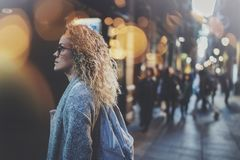 Pretty young woman hipster in stylish clothing wearing eye glasses traveling in the european night city. Bokeh and. Flares effect on blurred background stock images
