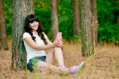Pretty young woman holdiing mobile phone and smile royalty free stock photos