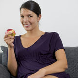 Pretty young woman holding an apple Stock Photos