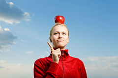Pretty young woman holding appleon the head Royalty Free Stock Images