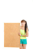 Pretty young woman holding blank cork board smiling. Pretty young woman holding blank cork board standing smiling , Girl holds noticeboard with advertising space Stock Image